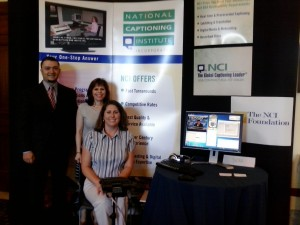 Anthony DeMarco, Connie Templin, and Darlene Parker pose in front of the NCI display