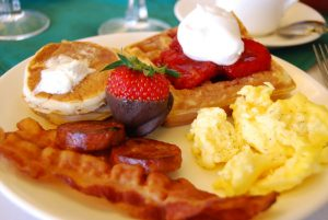 Breakfast plate with eggs, bacon, sausage, pancakes, a waffle, and a chocolate-covere strawberry