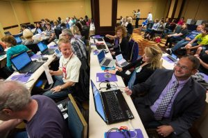 Contestants for the 2014 Realtime Contest before the contest begins. Many look congenial. They sit in rows with their laptops and steno machines in front of them. In the back are about a dozen observers.