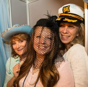 Three smiling women in funny hats