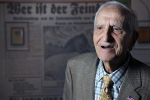 An elderly man is in the middle of speaking. He sits in front of a German newspaper projected behind him.