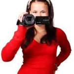 Girl holding a camcorder in front of her face; she seems to be smiling