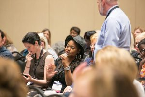 A woman speaks into a microphone. She is sitting amongst rows of people at a conference session.