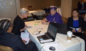 Four people sit around a table -- two are in coversation while the other two write the conversation on a steno machine and provide captioning