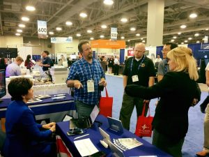 Set in a moderately busy vendor hall, two women in professional garb speak with a few men who are visiting the booth. One of the women is seated at a steno machine. On the table are flyers and propped up iPads.