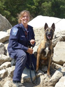 A woman in uniform poses, kneeling, next to a german shepherd mix dog on a leash