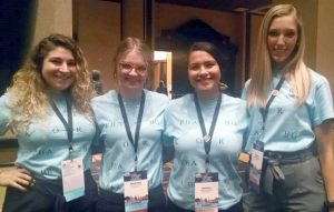 Four young women pose in matching light blue shirts with steno written on the front
