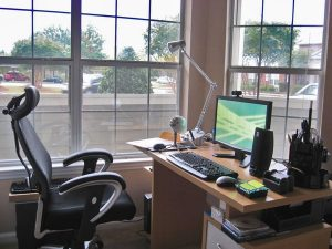Home office setup with a captains chair, desk, computer, etc.; the desk is in front of a wall of windows