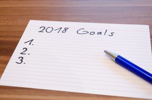 "pen and index card with ""2018 goals"" written at the top and a list"